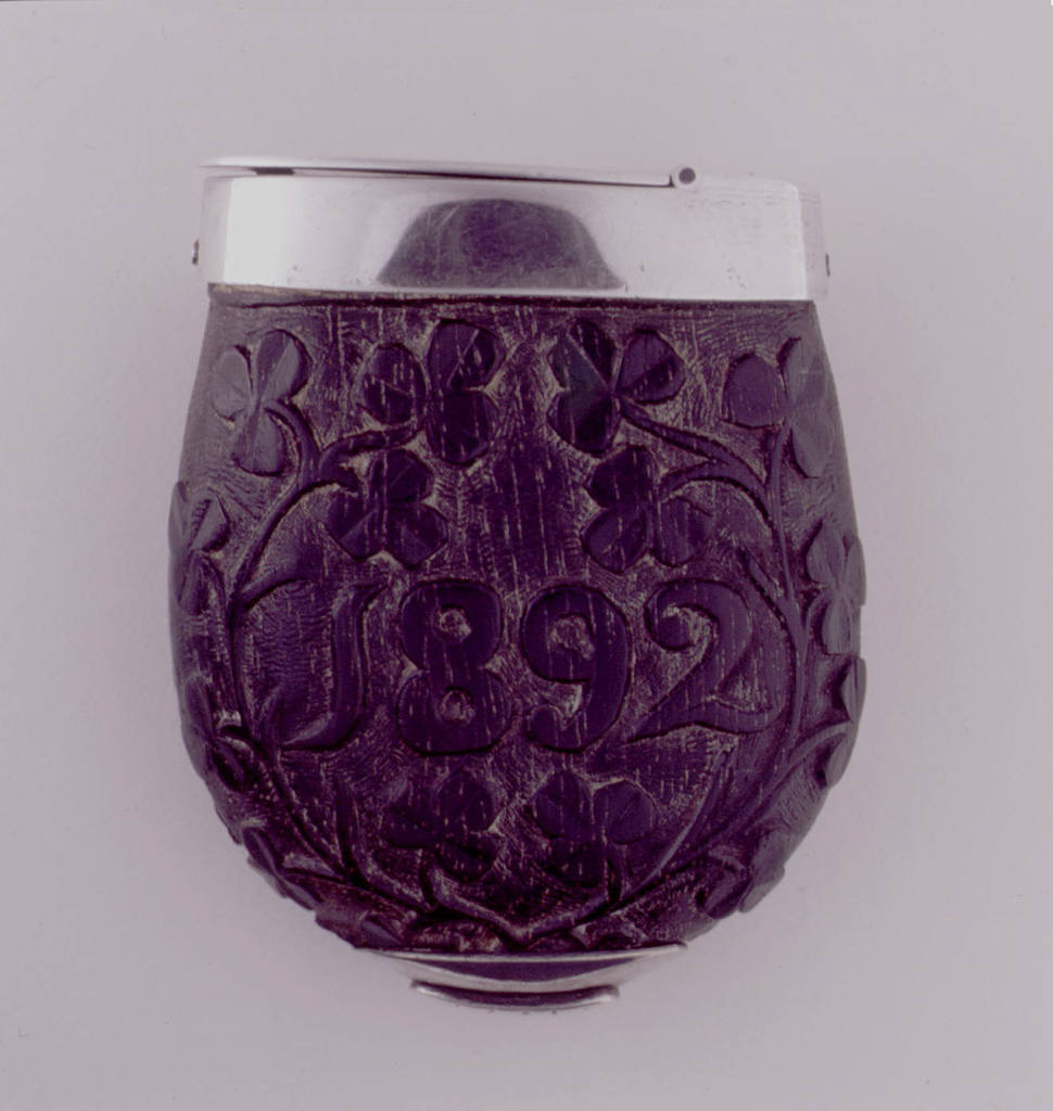 """Ovoid, with flat top surmounted by plated metal collar. Black/brown colored body features all over carved decoration of shamrock plants, """"1892"""" carved into front, central reserve, the monogram """"HR"""" carved into the reverse, central reserve. Flat, elongated, oval shaped, plated metal lid hinged on top of collar. Small, lozenge shaped, plated metal striker attached to underside of box."""