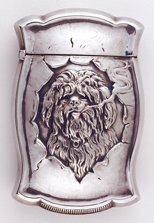 Rectangle form with bulging sides and flared corners.  The front has a plain silver surface with illusionary relief scene of head of hairy dog peering through ripped hole in safe.  Dog is smoking with smoke trails off to right side.