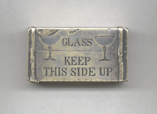 """Rectangular, in the shape of a wooden crate, featuring incised decoration of 2 champagne glasses on front, inscribed """"Glass, Keep This Side Up,"""" on top, long side inscribed """"Bollinger,"""" on bottom long side, inscribed """"Dry Extra Quality,"""" on left side """"E. &. J. B., 10.448,"""" on right side incised anchor with """"R.B. & C"""" at center and larger """"P."""" at lower, right-hand corner. Crate has simulated straps wrapped around each end and small incised marks resembling nail-heads on edges of sides. Lid hinged on left side. Striker on underside of box."""