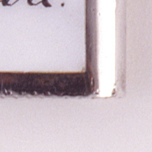 "Rectangular, with vertical sides curved, the front inscribed with the word/picture rebus ""Just one [pipe] more,"" the text in black enamel, image of a pipe in black, brown and white, all on a white ground. Reverse features elaborate, incised monogram (BW). Flat lid hinged on left. Striker on bottom."