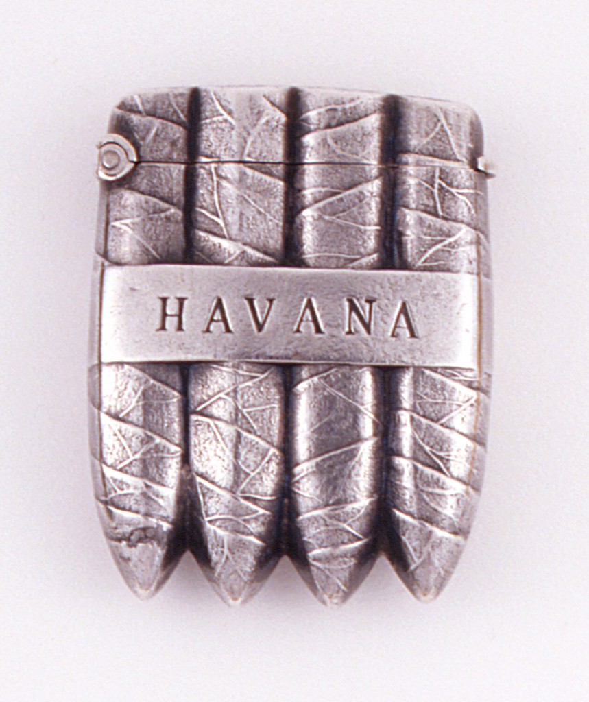 "In the form of four cigars held together with a band inscribed ""HAVANA"" on both front and reverse. Hinged on side. Striker recessed in top of lid."
