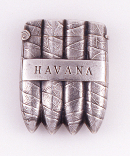 """In the form of four cigars held together with a band inscribed """"HAVANA"""" on both front and reverse. Hinged on side. Striker recessed in top of lid."""