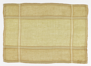 Tablemat with a windowpane effect in pale orange and pale yellow. Stripe effect is emphasized with a single cord outline.