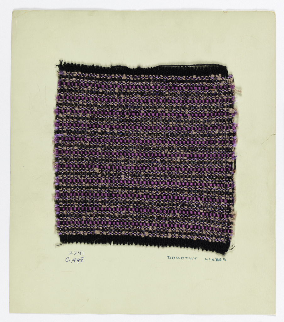Sample in shades of black, purple and pink with metallic accents. Warp is made of black two-ply yarns while the weft is comprised of purple two-ply yarns, metallic braid, shiny purple thread wound over a central core and pink boucle.