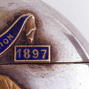 "Circular, silver-plated, with brass bust of Queen Victoria in profile facing left, above which is blue enamel swag inscribed ""In Commemoration."" In blue enamel boxes on bottom right and bottom left of swag, are the inscribed dates ""1837"" and ""1897."" Box lid, which displays enameled inscriptions, hinged on back. Striker on bottom."