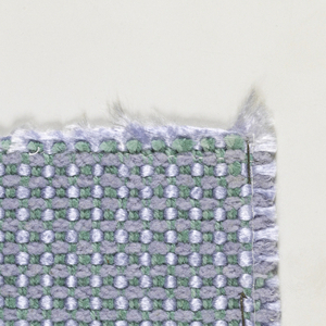Sample with green three-ply warp threads and weft threads of blue chenille and shiny blue yarn.