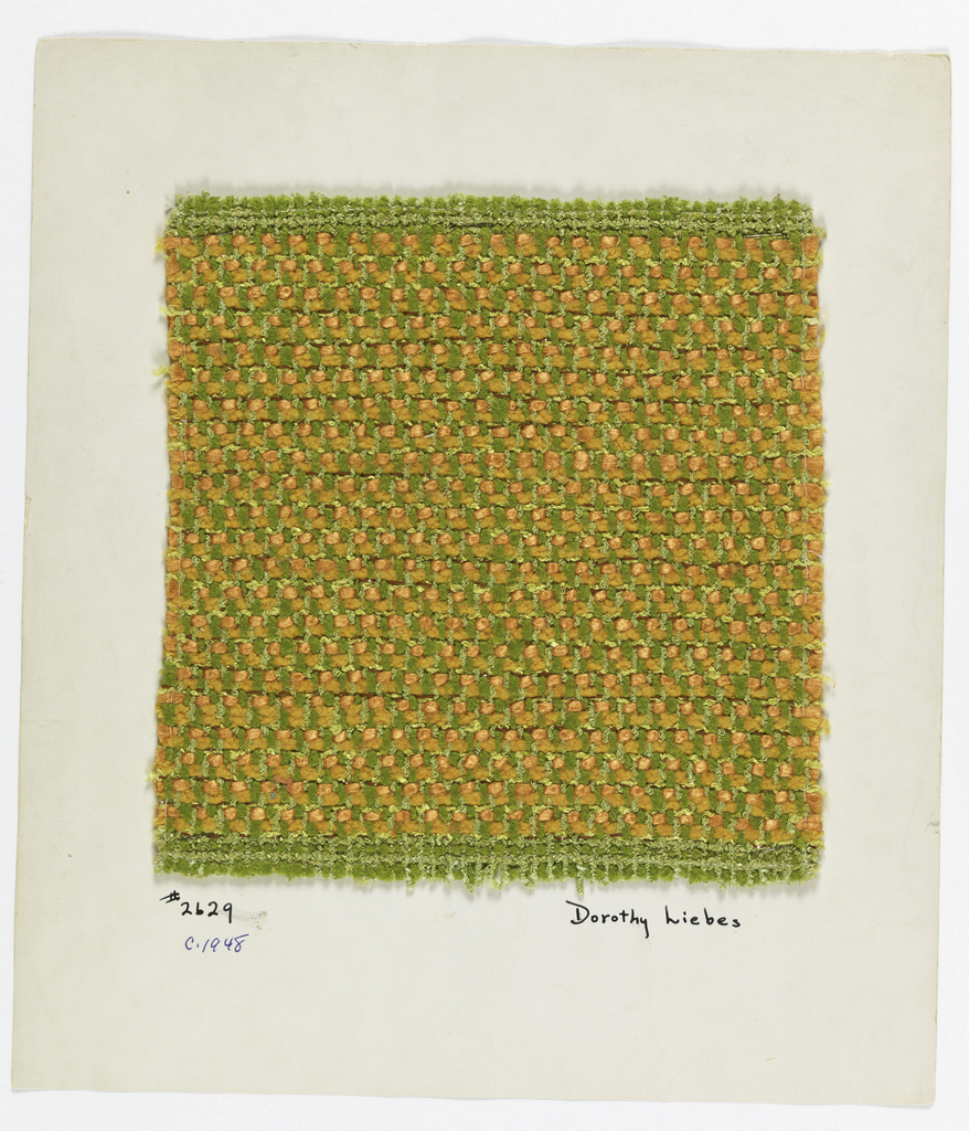 Heavy twill in green and orange. Warp is green boucle alternating with green 2-ply yarn. Weft is a repeating sequence of orange chenille, orange smooth yarn, and yellow boucle with flat brown plastic.