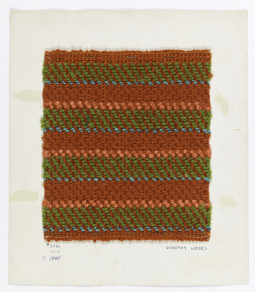 Heavy twill in red, orange, blue and dark green. Warp is orange 2-ply yarn alternating with red 2-ply yarn. Wefts have bands of red chenille, blue 2-ply yarns, green chenille in 2\2 twill and two wefts of red smooth yarn in 1\3 twill.