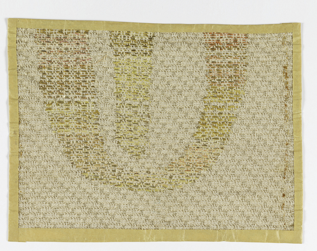 Hand woven sample with off-white warp and off-white and metallic gold wefts. The Hebrew letter shin is brocaded in metallic gold and shades of orange, pink and gold.