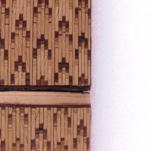 Rectangular form with rounded edges. Straw-work in chevron pattern over cardboard, veneered.  The fitted, removable, slip top reveals when removed, alternating dark/light vertical stripes in straw are evident on upper-portion of body. A sandpaper like striker is on the underside.