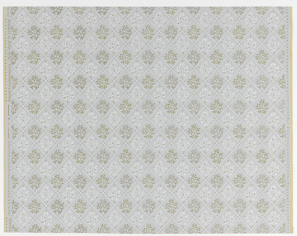 "Fine white lines forming diamond pattern on gray ground. Foliated twigs and dots alternating in gold and white fill diamonds. Printed on left selvedge:""Danske Tapetfabrikker A/S - 3836 - Made in Denmark""."