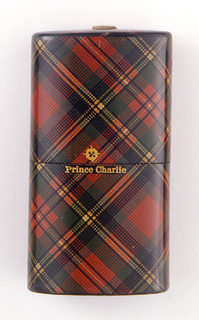 """Oblong, with long sides curved, covered in a tartan pattern printed paper in red, green, black, and yellow, as well as possible maker's mark and pattern name """"Prince Charlie"""" printed in gold on front. Slip top style lid meets box body at center. Small match socket in ivory on lid top. Striker of sandpaper on bottom."""