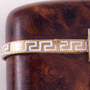 Rectangular, with rounded corners, curved sides, and slightly curved lid. Hollowed out section of burlwood features gold band that wraps around the circumference of lid's bottom edge, on which is a continuous Greek key design in white enamel. Lid catch on front features a small diamond square attached to gold and enamel band, from which a small diamond pendant is hinged, which snaps over a single diamond in order to lock lid shut. Reverse features two white enamel loops, each attached below a hinge. Oblong, cross-hatched, gold piece attached to bottom serves as striker.