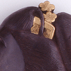 In the form of a geisha's head in profile, with finely rendered ceremonial hairdo that wraps from front to back, featuring an assortment of hair ornaments on top such as two gilded combs, two gilded and one ungilded flower, gilded string bow at back, gilded hair pin near bottom front. Release button on front of neck opens up brass rimmed bottom lid. Striker on underside of lid.