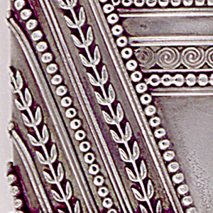 Rectangular, with rounded corners, featuring alternating, applied, diagonal bands of bead and leaf ornament, a horizontal band of bead and flower motifs directly beneath, as well as intersecting horizontal bands of bead and spiral motifs at opposite mid-section. All ornament wraps around box body. Undecorated surfaces are slightly mottled. Hinge located on lower corner so that box opens on the diagonal, seperating the bead, leaf, and flower ornament from the bead and spiral. When opened, an unadorned, interior match container is revealed, also attached at corner hinge, so that it may swing from side to side. Striker attached to one side of interior container.