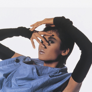 Photograph of a model wearing black arm sleeves, blue shirt dress, white short leggings, and black leg sleeves. Above, text in black caps: ISSEY MIYAKE 1987.