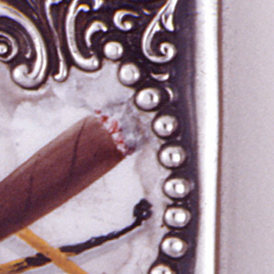 Rectangular, with rounded corners, featuring raised scroll and bead ornament, beads frame asymmetrical, enameled, central reserve depicting a burning, brown cigar, beneath which are two wooden matches, one of which is burnt. Reverse features same raised ornament, central reserve inscribed AJM. Lid hinged on side. Striker in recessed groove on bottom.