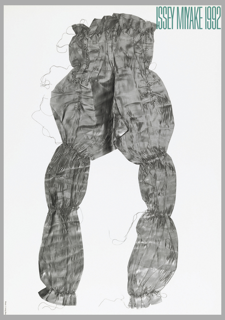 Photograph of a large costume in silver fabric; no model. Text in green, upper right: ISSEY MIYAKE 1992