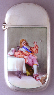 Oblong, with upper, lower parts and sides curved, featuring polychrome enamel decoration of gentleman, legs crossed and seated at table, dressed in 17th century costume smoking a clay pipe. He wears pale red 3/4 length jacket with white lace collar and blue sash draped diagonally across chest, pink knee pants, white stockings, pink Louis XIV style shoes. Table is covered with lace trimmed white cloth, on which sits his pink broad rimmed hat with large white feathers attached. He appears to be sitting on a green-yellow throw that is draped on seat of chair. Plain background is light gray. Reverse undecorated. Lid hinged on left. Striker in small oval recess on box bottom.