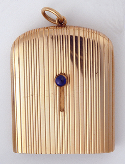 Oblong, with curved bottom, and straight edged top from which emerges a retractable match compartment. Overall surface decoration features alternating grooves of six narrow and three slightly wider bands, slot on front center of body where a cabochon sapphire knob may be moved upwards, allowing top to rise up, out and fall backwards on interior hinge, while simultaneously raising the inner compartment, from which matches may be pulled. When closed, a recessed serated edge on top's exterior serves as striker. Link attached to bottom.