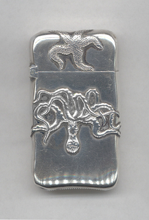 """Oblong, curved sides and corners, featuring raised decoration of upside-down octopus on body, starfish on lid, monogram """"MR"""" on reverse. Lid hinged on side. Striker on bottom."""
