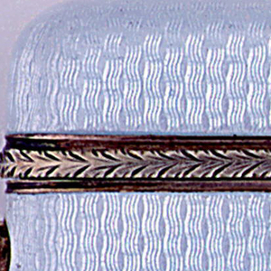 Rectangular, with rounded corners, featuring transluscent pale blue enamel over an engine turned ground, revealing repeating, vertical, wavy lines. The lid's lower edge is banded with pink and yellow gold acanthus leaf border. Lid released by pushing cabochon pink sapphire button at side. Lid hinged on opposite side of sapphire. Striker in recessed gold groove on bottom.