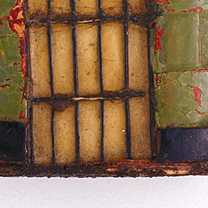 Oblong, curved vertical sides, featuring woven and applied strips of cardboard, painted and varnished to resemble a bricked prison cell entrance. Rectangular, recessed doorway has grid of fine threads, simulating cell bars, black cornice-like band over door, number 43 painted in yellow at left of doorway; lower third of wall area woven and painted green, bordered above and below with black bands, upper 2/3 of wall area woven and painted red. Slip-top cover (upper third of box) when closed meets black overdoor band, lid may also be removed entirely. Striker of sandpaper on box bottom.