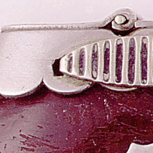 Circular, with flat top, assembled from a hollowed out tropical bean pod, the top of which is capped with a scalloped metal collar, over which a flat, hinged lid is attached. On front and reverse of collar small oval strikers are attached horizontally. Slight indentation in center of seed where a small, unadorned, metal shield is attached.