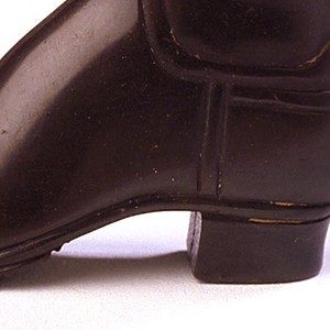 """In the shape of a tall black boot, inscribed in light brown """"Compliments of Hood Rubber Company, Boston, U.S.A."""", with slip-top lid, which may be removed entirely. Striker on grooves of sole on boot bottom."""