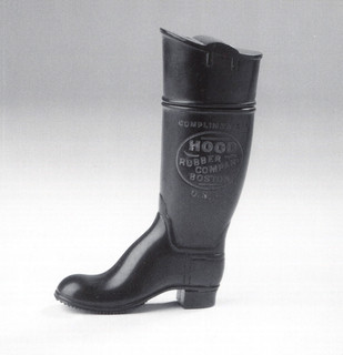 "In the shape of a tall black boot, inscribed in light brown ""Compliments of Hood Rubber Company, Boston, U.S.A."", with slip-top lid, which may be removed entirely. Striker on grooves of sole on boot bottom."