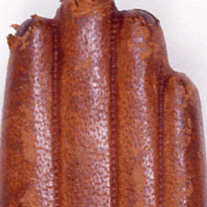 In the form of a light brown leather glove, the leather tooled to simulate stitching. Lid hinged on bottom side. Striker on brass plaque on bottom.