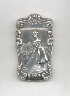 Oblong, with curves and counter-curves around perimeter, featuring raised decoration of female golfer in hat and long dress at tee, on grass course, with building and hills in background, c and s-scroll edges and flower at top center of lid. Lid hinged at side. Striker at bottom.