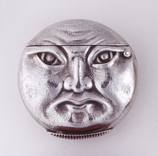 Circular, featuring a full moon face on front, reverse features a bat flying among cloud formations. Lid hinged on upper side. Lozenge shaped striker on bottom.