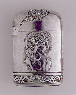 Oblong, curved corners, featuring central bust of Bacchic figure with grapevine diadem, below which is band with egg and dart motif, above, on lid, is broken edged, ruin-like element. Reverse features busts of Mars with helmut and shield, and Diana, amid various classical motifs and ruin-like element. Lid hinged on side. Striker on bottom.