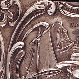 """Oblong, curved sides, featuring raised decoration of male figure skater in 19th century dress, muff over hands, boy on sled, harbor background with sail boats, coastal buildings, all framed by c-scrolls and floral motifs, stamped """"ALPACCA"""" near top, as well as unidentified maker's mark just below. Reverse features pastoral scene with 2 females in 19th century country dress, hoisting bags on to donkey's back, sheep and dog nearby, church in background, all framed by c-scrolls. Interior match container slides out of external, decorated sleeve, small thumb catch near top edge. Striker on top side."""