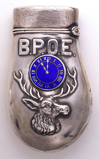 Oblong, in the shape of an Elk's tooth, featuring a blue enameled clock dial with Roman numerals and set at 11:00, beneath which is a raised image of an elk's head, above the clock are the letters B.P.O.E., an acronym for the Benevolent and Protective Order of Elks. No decoration on reverse. Lid hinged on upper left. Striker on the reverse side of lid.