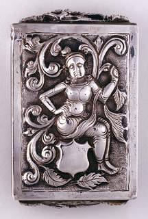 Rectangular, featuring raised decoration of Eastern Indian goddess seated on undecorated shield, surrounded by swirling foliate motifs. Reverse features goddess standing next to palm tree. Female with upraised arms on lid, as well as bottom. Lid hinged on side. Striker on each vertical side.