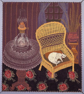 Embroidered picture showing white cat asleep in a wicker chair beside a table with a lace cover and oil lamp, a window and plant stand in the background, on a carpet with large roses.