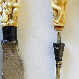 Blade sabre-shaped with rounded point; silver ferrule. Ivory handle carved in deep relief. Three putti, one of them kneeling, the other two climbing on top of his shoulders.
