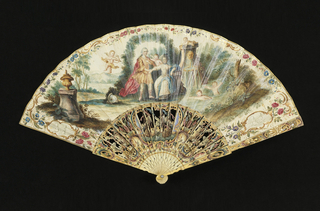 Pleated fan with painted paper leaf. Obverse mount shows a couple – the woman is seated, and the man stands under an arbor by a fountain with two bathing cupids. One cupid is shooting an arrow at the couple. In cartouches at either end are two cupids in monochrome. The reverse has a central monogram with cupids in cartouches at either end. Sticks are elaborately carved with openwork (à jour), painted and gilded. The center shows a naval battle, and on either side trophies and soldiers storming two towers with a cannon.