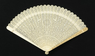 Brisé fan with carved ivory sticks. A monogram in an oval medallion at the center is flanked by pagodas on either side. The ground is filled with an overall design of small flowering vine and birds, with a lace-like effect achieved by the carving of fine vertical lines to create a sheer ground for the solid motifs.