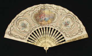 "Leaf of painted buff silk. Obverse: three medallions, the central one containing landscape scene; ground decorated with brown and red lines and appliquéd with sequins. Reverse: medallion of ribbon and music trophies. Pierced, gilded and painted ivory sticks. White paste jewel and metal bail at rivet. In box painted in similar manner as fan with wreaths of roses, blue ribbon, trophies and green vine, with light blue lining. Marked in gold, ""Creusy 28 Rue Meslay Paris""."