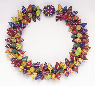 Necklace cord threaded with projecting multi-colored thorn-like beads, reminiscent of candies with spirals; at the back, knot-like element in black with yellow and red teardrops.