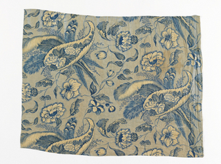 Fragments of valance or bed skirt. Thin woven cotton with repeating floral pattern in blue on yellow. Dominant design feature is a large curled leaf containing cut flowers. Background printed with minute dots giving almost solid effect. Diagonally oriented design.