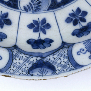 Circular plate painted in underglaze blue on white; center with chinoiserie scene of flowers, rocks, insects; cavetto with 14 uniform panels with flowers; rim decorated with evenly spaced reserves of floral motifs on diaper pattern; 7 groups of 4 blue dots painted on underside of rim; low foot rim.