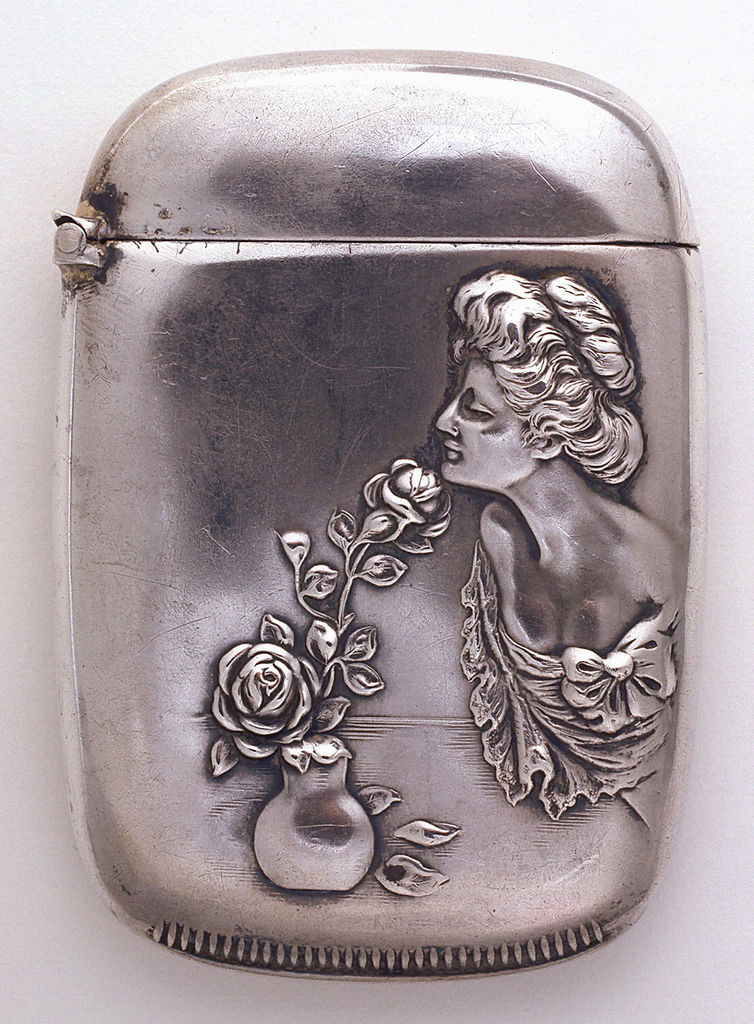 Oblong, curved sides, rounded corners, featuring raised decoration of Gibson Girl with upswept hair and low cut dress, leaning forward to smell roses in small vase on table top, identical decoration on reverse. Lid hinged on side. Striker on bottom.