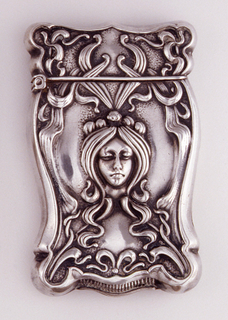 Rectangular, curved corners, sides, top and bottom curved and cinched at several points, featuring female mask with long hair and long, stylized tendrils, all framed by stylized, intertwined ribbon-like ornament. Reverse features open, central reserve with monogram GMM, all framed by series of attenuated lily flowers. Lid hinged on side. Striker on bottom.