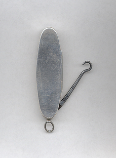 Elongated oval shape, flat, undecorated front and reverse surfaces, featuring small knife and button hook that swing out from left and right concealed slots on underside. Link attached to end. Lid (box cover on front) hinged on long, button hook side. Striker also on long side beneath hinge.