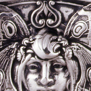 Rectangular, with curved corners, top, bottom, and sides, featuring female mask with pendant earrings, long hair tendrils, and butterfly wings framing her face, smaller butterflies above, on lid, and below. Reverse features open reserve with monogram HB, framed by stylized curves and butterflies. Lid hinged on side. Striker in recessed groove on bottom.