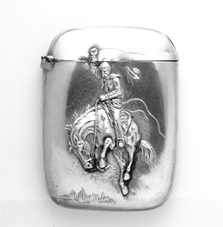 Rectangular, with rounded corners and sides, featuring raised decoration of cowboy on bucking horse, reins in his left hand, whip in raised right hand, to left is hat flying off his head. Reverse side undecorated. Hinge on side. Striker on bottom.